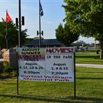 A sign in Cortesi Veterans Memorial Park lists upcoming concerts on Thursdays in August and movies on Mondays in August.