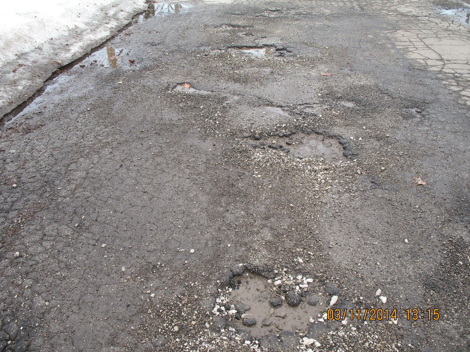 Potholes and Cracks in Asphalt of a Street